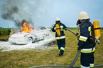 Two firefighters fighting fire on grey station wagon on field during daytime