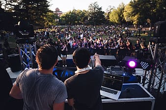 Two men on stage with people watching at daytime