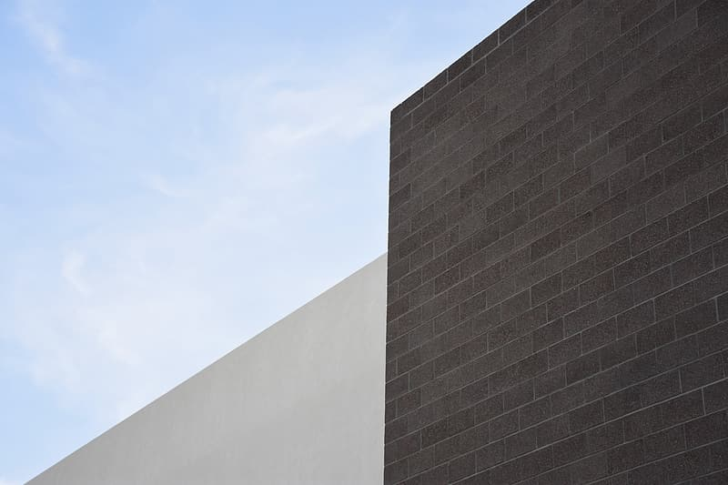 Brown concrete bricked wall under cloudy sky