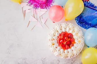 White cake with red sliced fruit beside yellow and blue balloons