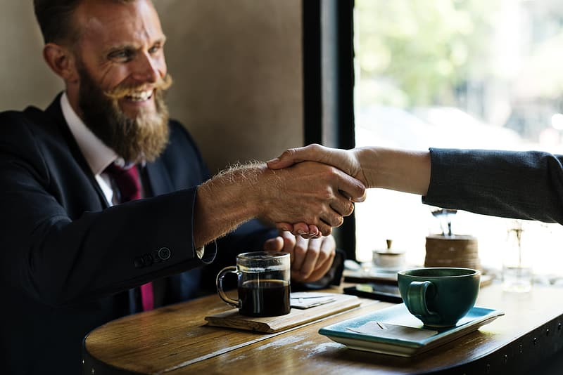 Man in black suit in front of coffee on table shaking hands on person in other side