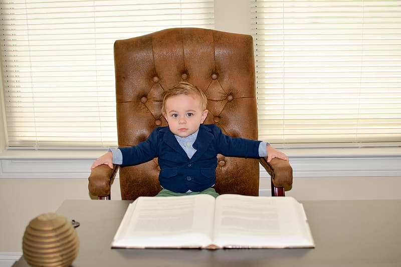 Boy sitting on office chain in front of book