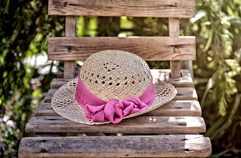 Brown wicker hat with pink ribbon on top of brown wooden chair