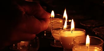 Person lighting votive candles