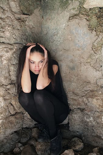 Woman in black pants crouching near rocks
