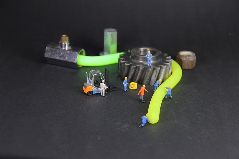 Assorted-color plastic toys beside gear and cable