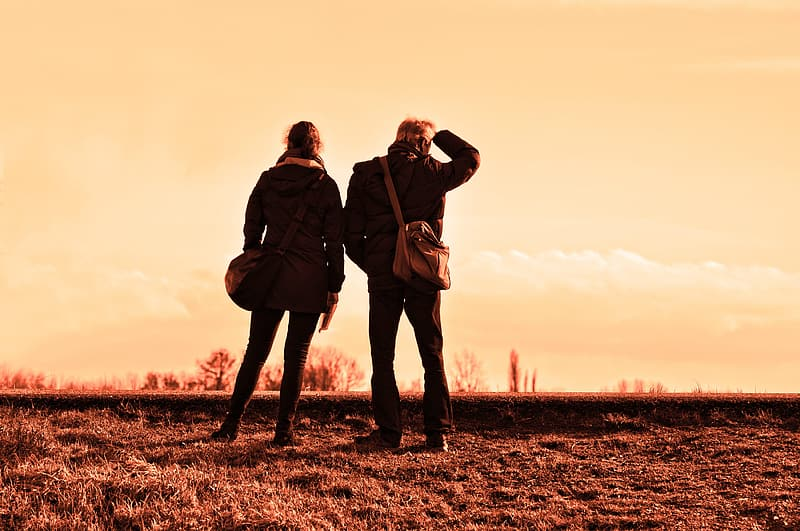 Two person standing on brown open field during golden hour