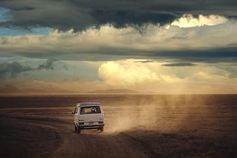 White suv on brown sand under white clouds during daytime