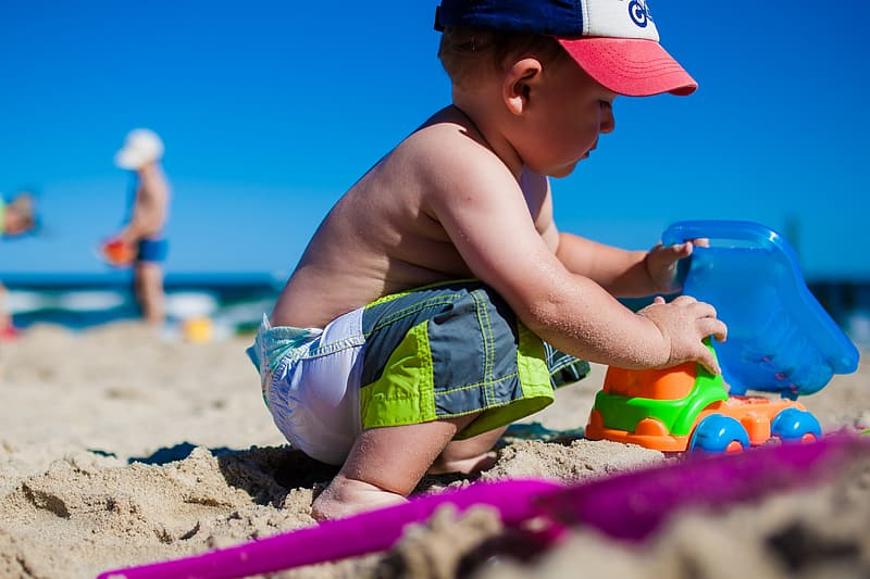 Boy playing toy on white sand