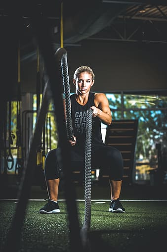 Woman holding rope on gym