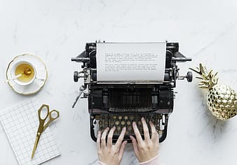 Person holding black typewriter on white table
