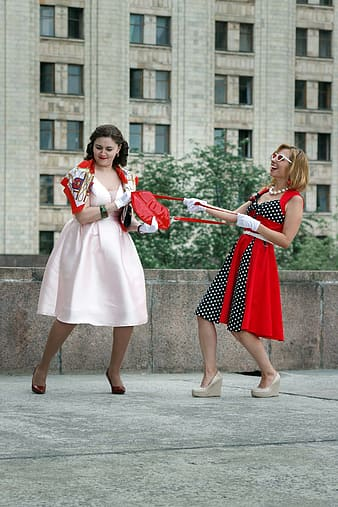 2 women in white and red dress holding red and white flag