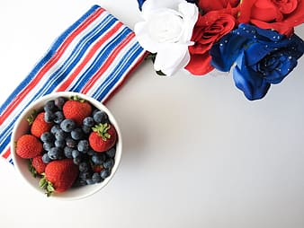 Blueberries and strawberries in white bowl on white surface