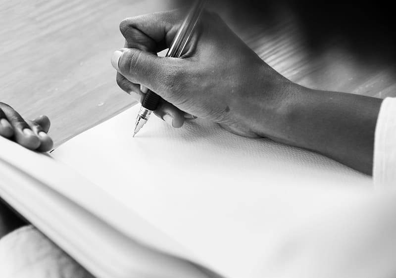 Person writing on paper in grayscale photography