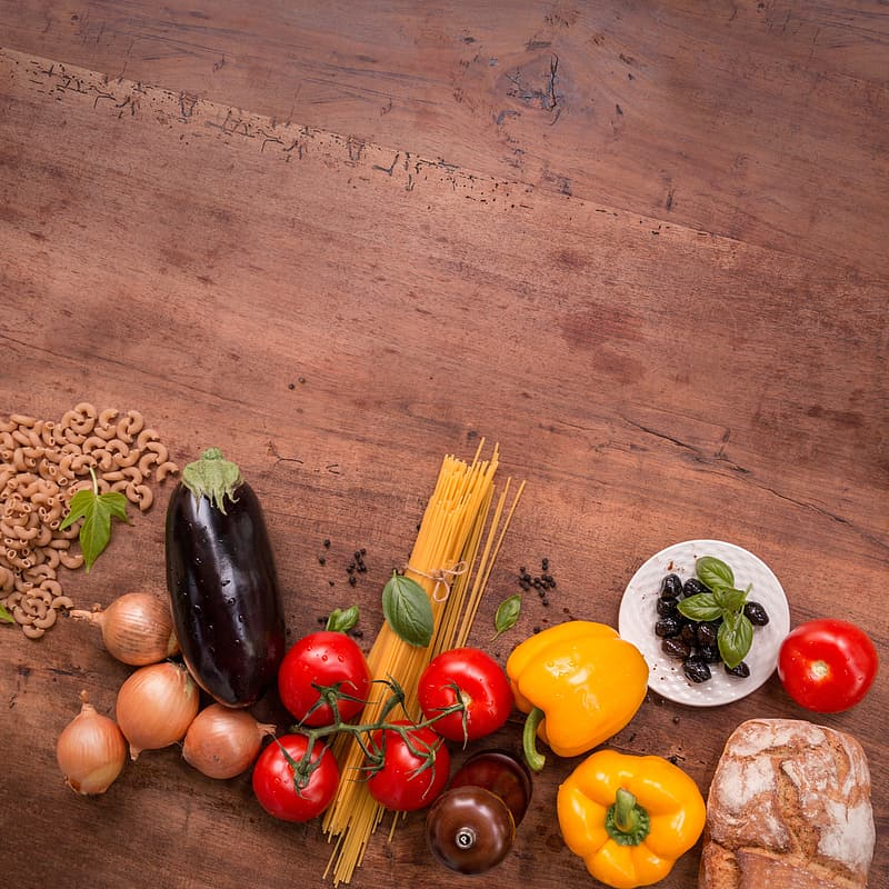 Top view of a bunch of assorted vegetables on brown wooden surface