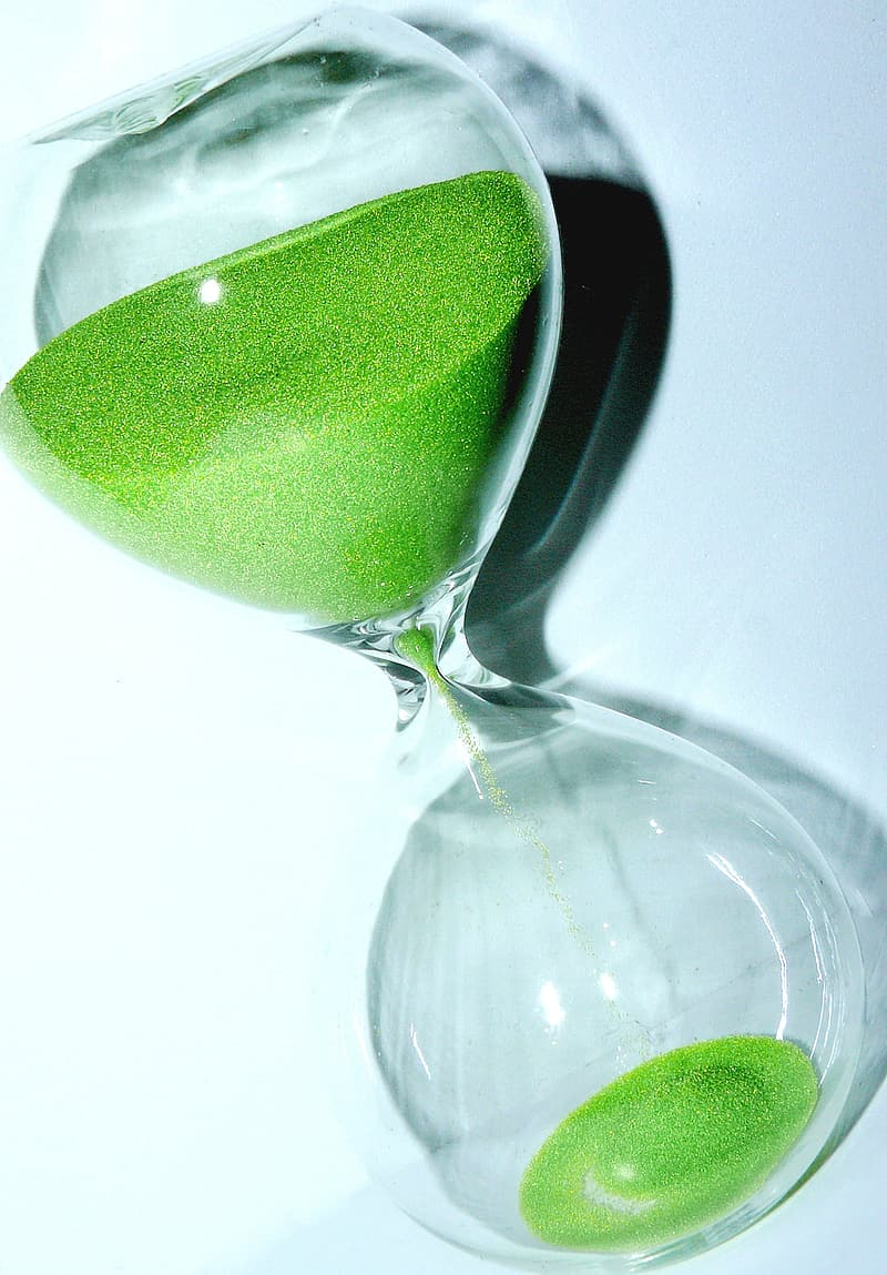 Clear and green hourglass on white surface