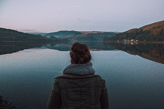 Person standing front of body of water