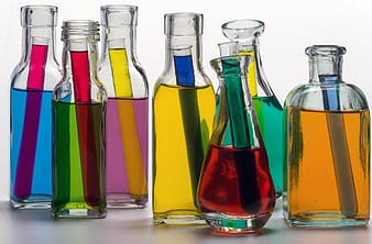 Clear glass containers filled with assorted-color liquids