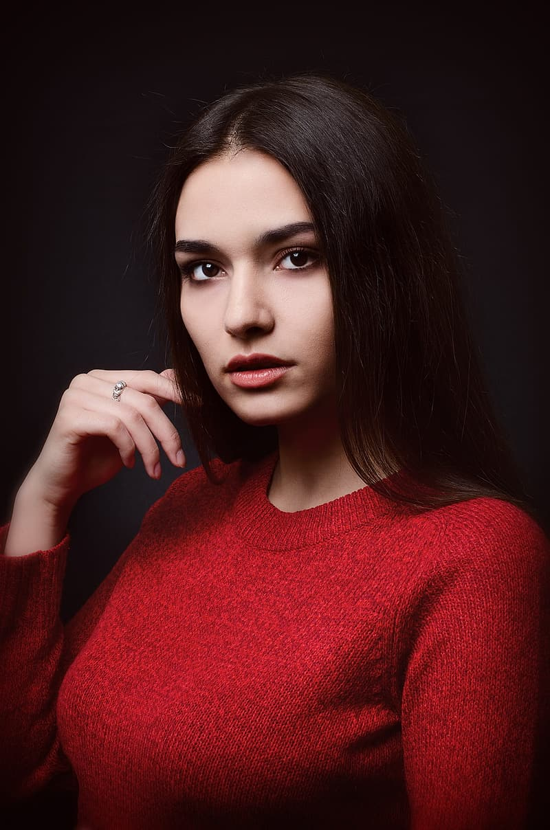 Woman in red sweater holding her hair