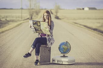 Photograph of woman sitting on brown box beside desk globe on white briefcase center of road