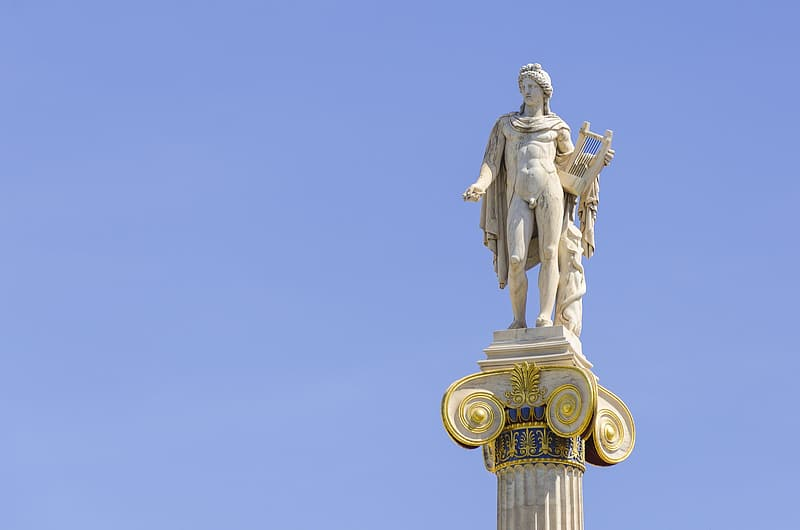 Gold statue of man under blue sky during daytime