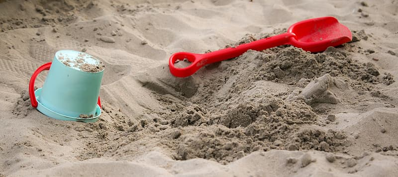 Macro photography of blue plastic bucket and red plastic shovel on sand