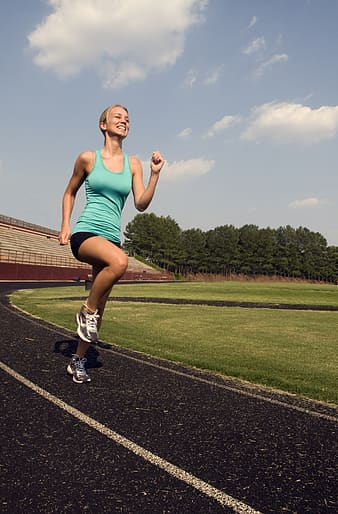 Women in blue tank top running on track field during daytime
