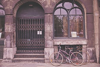 Two bicycles against brown building