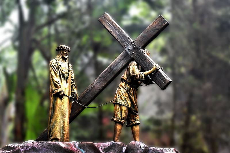 Person carrying cross near man standing figurines