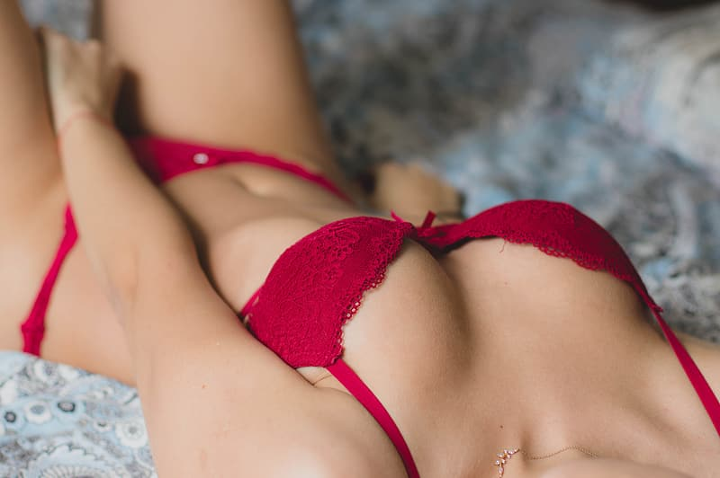 Woman in red brassiere lying on white textile