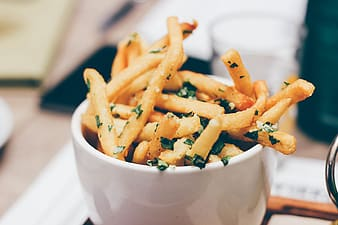 Shallow focus photography of fries filled white ceramic bowl