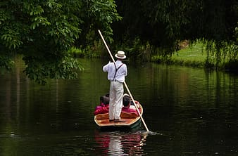 Man rowing on boat with passengers sitting