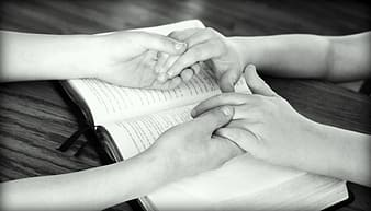 Grayscale photography of two person holding hands on book