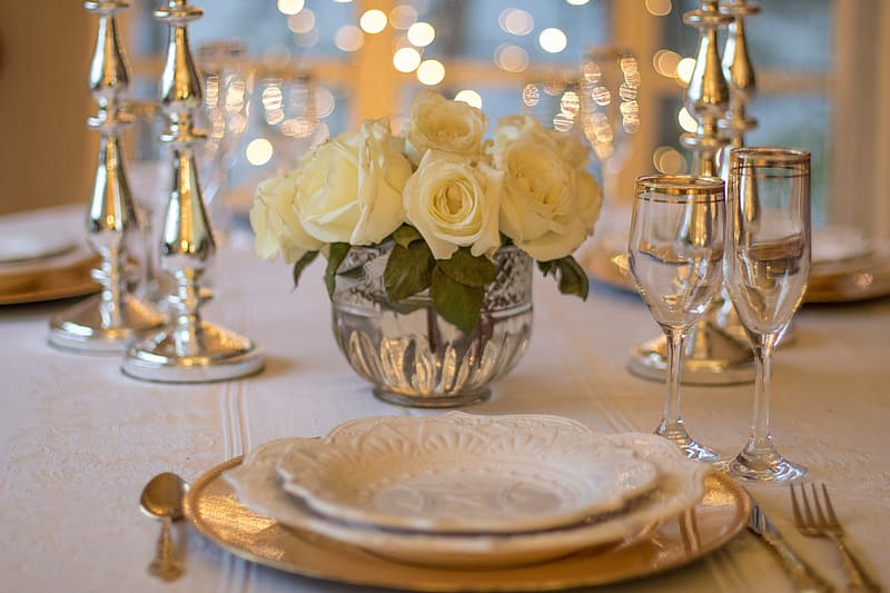 White roses with clear glass champagne flute and white ceramic plate