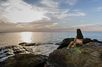 Woman sitting near rock formation in front of sea