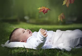 Photograph of baby lying on grass with leaf smiling