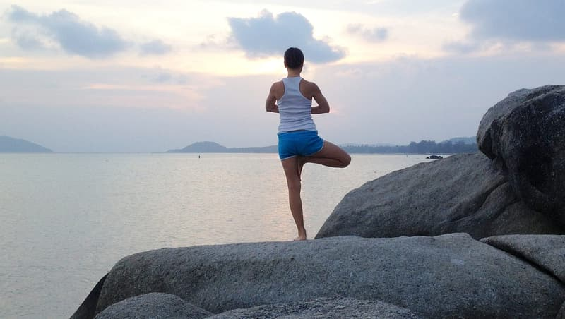 Woman wearing white racerback tank top with blue shorts standing on rock near body of water during daytime