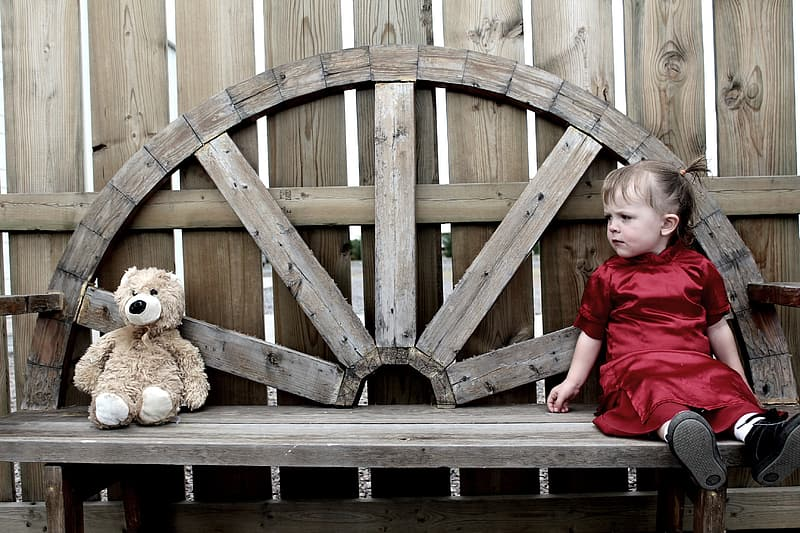Girl sitting on brown wooden bench while looking at brown bear plush toy