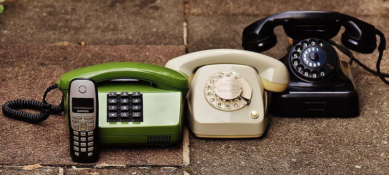 Green, white, and black corded telephones