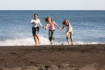 Three girls running away from ocean wave on the beach