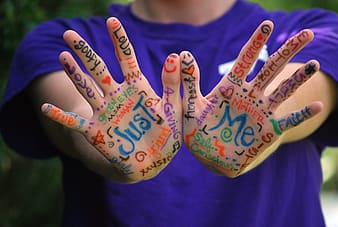 Person wearing purple crew-neck t-shirt with hand art