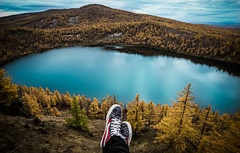 Person wearing red-and-white sneakers sitting in front lake