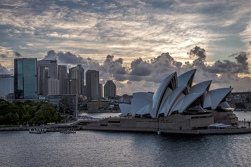 Sydney opera house near body of water under cloudy sky during daytime