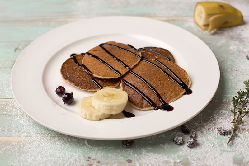 Plate of pancakes with chocolate syrup and sliced banana