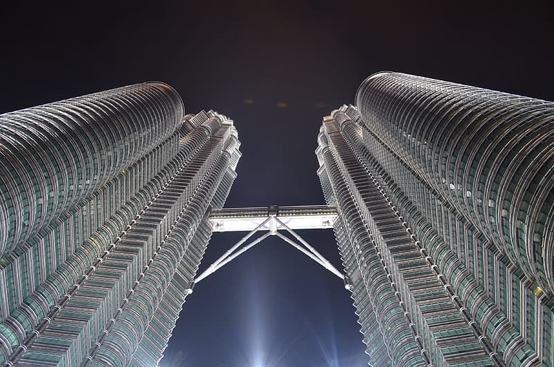 Low angle photography of twin tower during night time