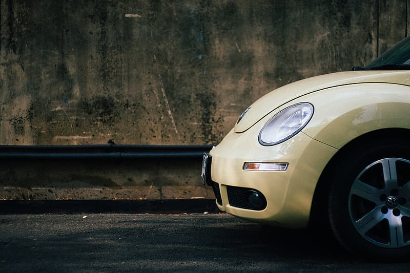 Yellow Volkswagen New Beetle parked on side of street