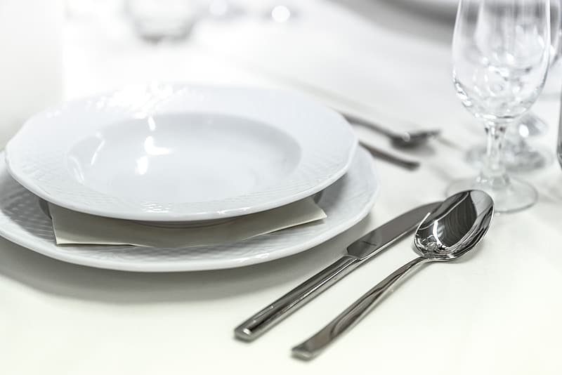 Photo of stainless steel knife beside white ceramic plate