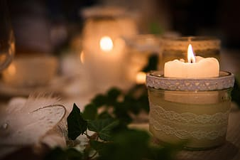 Lighted white tealight candle in closeup photography