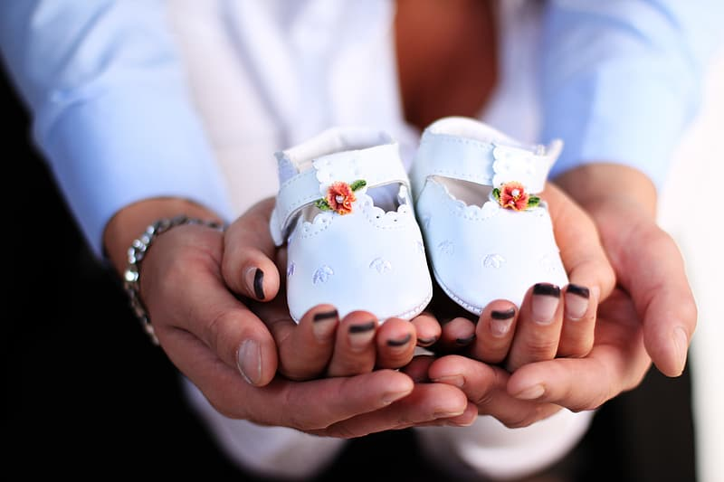 Close-up photography of pair of baby's white leather shoes on persons hand