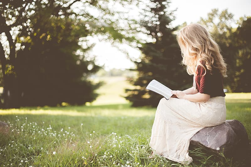 Girl in white dress reading book on green grass field during daytime